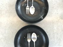 Finished eating of two sets of silver stainless spoon, fork and black ceramic plate. Two sets of silver stainless spoon, fork and black ceramic plate which Royalty Free Stock Photos