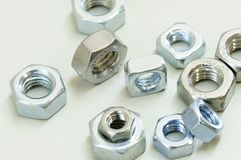 Finished Hex and square nut, most common shape of fastener. Used in conjunction a mating bolt to fasten multiple parts together. Horizontal color image stock photography