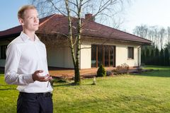 Finished house. Young handsome architect standing in front of finished house royalty free stock photo