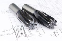 Finished metal reamer tools. Two finished metal reamer tools with protective coating lying on blueprint drawing Stock Image