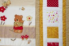 Finished quilt with tiny bear. Patchwork quilt decorated with tiny bear Royalty Free Stock Photography