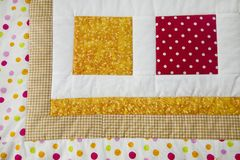 Finished quilt with tiny bear. Patchwork quilt decorated with tiny bear Stock Photo