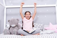 Finished reading book. Girl child sit bed with teddy bear finished reading book. Kid ready to go to bed. Finally. Finished that book. Girl kid long hair cute royalty free stock images