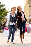 Finished with shopping. Two young girls shopping in the sunny weather Royalty Free Stock Photography