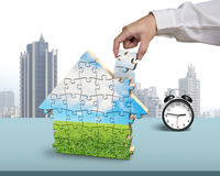 Finishing assembling house shape puzzles with alarm clock. In office Royalty Free Stock Photo