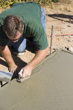 Finishing concrete. Man works with a trowel to smooth the finish on wet concrete stock images