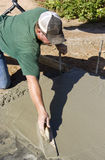 Finishing concrete. Man works with a trowel to smooth the finish on wet concrete royalty free stock photography