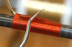 Finishing a custom guide wrap. This display shows how to finish a wrap on a rod guide on a custom fishing rod. A smoothing tool is used to give the wrap strength Royalty Free Stock Photos