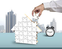 Finishing house shape puzzles assembling. In office Royalty Free Stock Photos