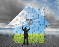 Finishing house shape puzzles assembling on pier with flood. And cloudy sky Royalty Free Stock Photo