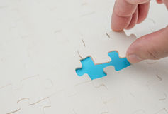 Finishing the last piece of jigsaw puzzle game on blue royalty free stock image