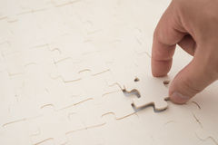 Finishing the last piece of a jigsaw puzzle game Stock Photo