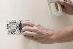 Finishing new house, light switch. Man finishing a house, fitting light switch cover Stock Images