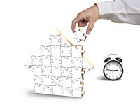 Finishing to assemble house shape puzzles with alarm clock. In white Stock Image