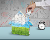 Finishing to assemble house shape puzzles. In office Royalty Free Stock Photo