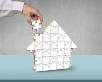 Finishing to assemble puzzles in house shape Royalty Free Stock Photography