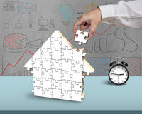 Finishing to assemble puzzles in house shape. With doodles background Stock Image