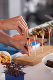Finishing touch. Hand of female chef preparing a small amuse on a stick Stock Photo