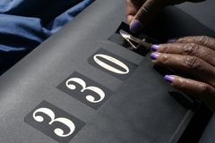 Finishing Touch. A pair of female African American hands applying address numbers to a mailbox Stock Photography