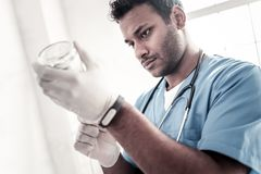 Focused doctor adjusting drip at hospital. Finishing touches. Concentrated male medical worker preparing a drip for his patient and adjusting everything at Stock Photography