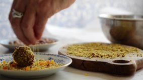 Finishing touches to handmade chocolate truffle as it is dipped in chocolate and rolled in almond, pistachio and diced apricot stock footage