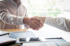 Finissant une r?union, poign?e de main de deux hommes d'affaires heureux apr?s l'accord contractuel de devenir un associ?, de col image stock