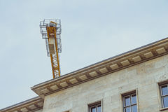 Finissez une partie de grue de construction jaune au-dessus de toit de buildi de bureau photographie stock