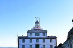 Finisterrevuurtoren met zonsonderganglicht en schaduwen Rode en blauwe kleuren, duidelijke hemel Galicië, Fisterra, Spanje stock afbeelding