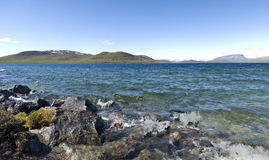 Finland. Panorama of a lake and snow caped mountains in Finland Royalty Free Stock Photo