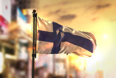 Finland Flag Against City Blurred Background At Sunrise Backligh Stock Photography