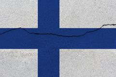 Finland flag on concrete wall with crack. Patriotic grunge background. National flag of Finland royalty free stock images