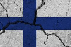 Finland flag on the cracked earth. National flag of Finland. Earthquake or drought concept stock images