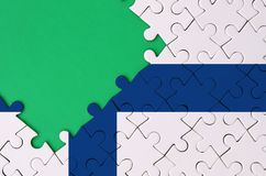 Finland flag is depicted on a completed jigsaw puzzle with free green copy space on the left side.  stock illustration