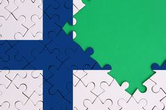 Finland flag is depicted on a completed jigsaw puzzle with free green copy space on the right side.  royalty free illustration
