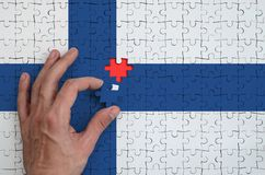 Finland flag is depicted on a puzzle, which the man`s hand completes to fold.  stock photo