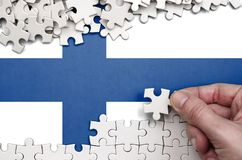 Finland flag is depicted on a table on which the human hand folds a puzzle of white color.  stock photos