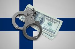Finland flag with handcuffs and a bundle of dollars. Currency corruption in the country. Financial crimes.  stock photo