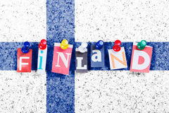Finland flag. Message Finland made of newspaper letters, hanged with thumbtacks at cork board edited that looks like national flag Royalty Free Stock Images