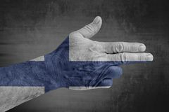 Finland flag painted on male hand like a gun. On concrete background royalty free stock photos