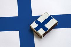 Finland flag is pictured on a matchbox that lies on a large flag.  royalty free stock images