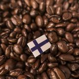 A Finland flag placed over roasted coffee beans.  stock images