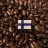A Finland flag placed over roasted coffee beans.  royalty free stock image