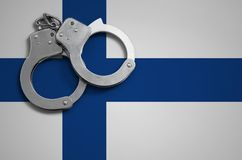 Finland flag and police handcuffs. The concept of crime and offenses in the country.  stock images