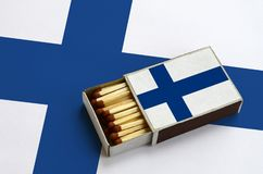 Finland flag is shown in an open matchbox, which is filled with matches and lies on a large flag.  royalty free stock photos