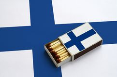 Finland flag is shown in an open matchbox, which is filled with matches and lies on a large flag.  royalty free stock photography