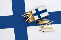 Finland flag is shown on an open matchbox, from which several matches fall and lies on a large flag.  stock photos