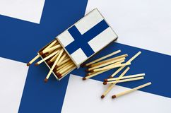 Finland flag is shown on an open matchbox, from which several matches fall and lies on a large flag.  stock photo