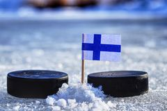 A finland flag on toothpick between two hockey pucks. A finland will playing on World cup in group A. 2019 IIHF World Championship. In Slovakia stock photos