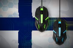 Finland flag and two mice with backlight. Online cooperative games. Cyber sport team. Finland flag and two modern computer mice with backlight. The concept of stock image