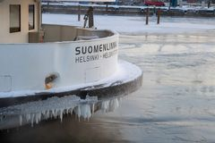 FINLAND, HELSINKI - JANUARY 2015: Local ferry to Suomenlinna in winter parked in ice royalty free stock photos